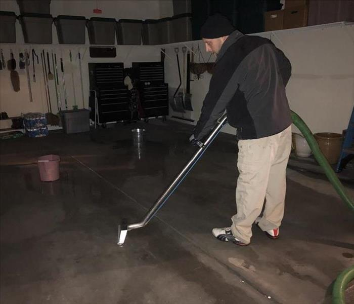 Technician steam cleaning the floor in a garage