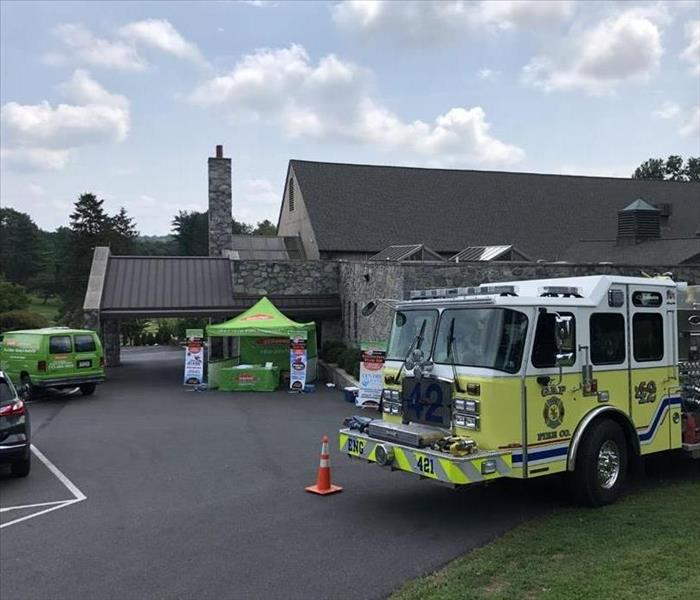 A SERVRO van, SERVPRO tent, and a firetruck outside of a building