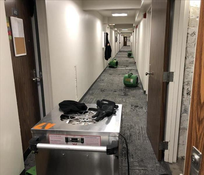 A dehumidifier and three air movers in a long hallway