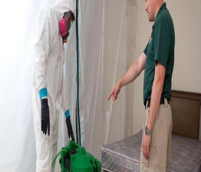 A manager and a technician in TYVEK suit in a bedroom at a mold job